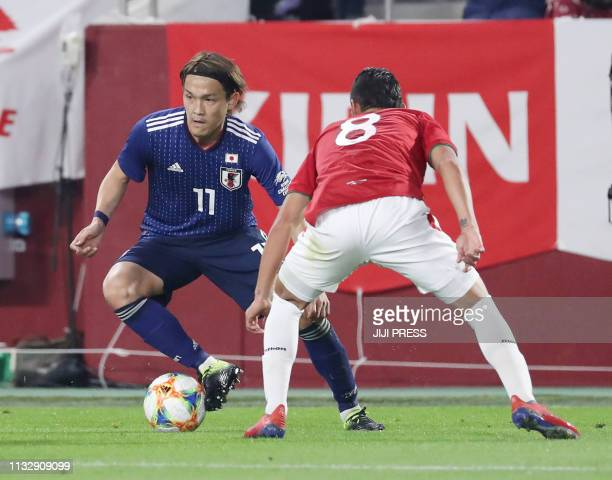 Japan's midfielder Takashi Usami and Bolivia's defender Saul Torres fight for the ball during their international friendly football match in Kobe on...