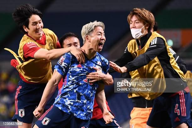 Japan's midfielder Takuma Asano celebrates with his teammates after Australia's defender Aziz Behich scored an own goal during the 2022 Qatar World...