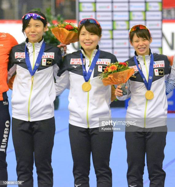 Japan's Miho Takagi Ayano Sato and Nana Takagi pose for photos after winning the women's team pursuit event at the world single distance speed...
