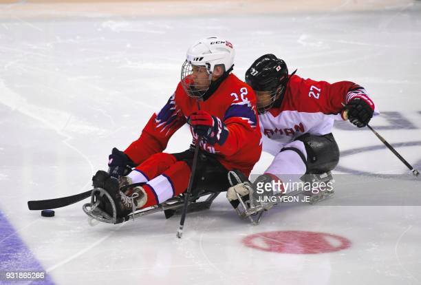 Japan's Mikio Annaka and Norway's Magnus Bogle fight for the during in the ice hockey classification game between Norway and Japan at the Gangneung...