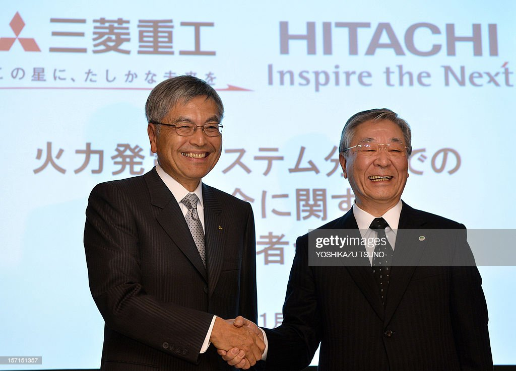 Japan's Mitsubishi Heavy Industries president Hideaki Omiya (L) shakes hands with Hitachi president Hiroaki Nakanishi at a press conference in Tokyo on November 29, 2012. Japanese industrial firms Hitachi and Mitsubishi Heavy Industries said on November 29 they would merge their thermal power businesses by 2014 as they take on global giants Siemens and General Electric. AFP PHOTO / Yoshikazu TSUNO