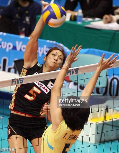 Japan's Miyuki Takahashi spikes the ball over Thai blocker Pleumjit Thinkaow during their second round match of the women's World Cup volleyball...