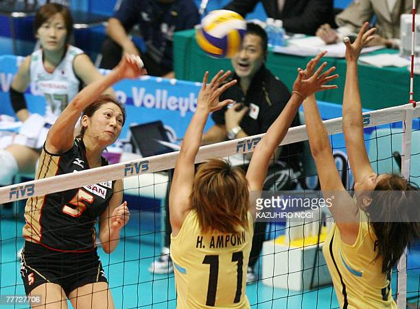 Japan's Miyuki Takahashi spikes the ball over Thai blockers, Amporn Hyapha and Symai Paladsrichuay during their second round match of the women's...