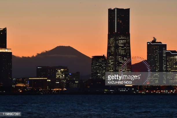 Japan's Mount Fuji is seen past skyscrapers at dusk from the Daikoku Pier Cruise Terminal, where the Diamond Princess cruise ship is anchored with...