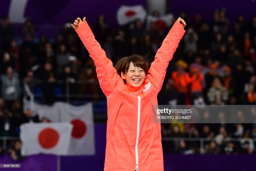 TOPSHOT - Japan's Nana Takagi celebrates her gold medal win on the podium during the women's mass start speed skating event medal ceremony during the Pyeongchang 2018 Winter Olympic Games at the Gangneung Oval in Gangneung on February 24, 2018. / AFP PHOTO / Roberto SCHMIDT