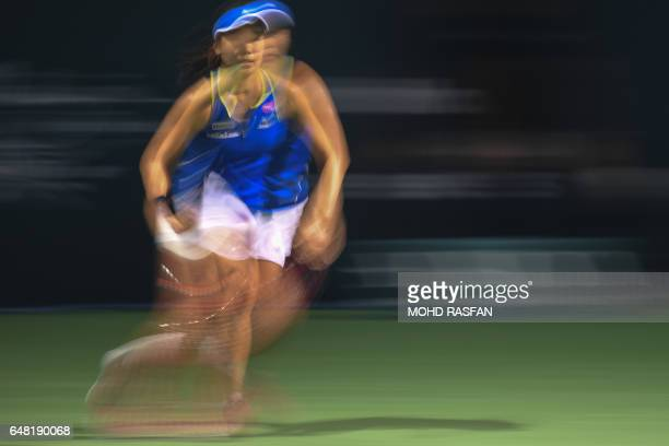 Japan's Nao Hibino runs for a return against Ashleigh Barty of Australia during their women's singles finals match of the WTA Malaysian Open tennis...