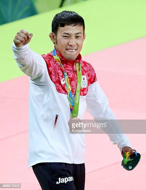 Japan's Naohisa Takato celebrates winning the bronze medal at the award ceremony for the men's 60-kilogram judo at the Rio de Janeiro Olympics on...