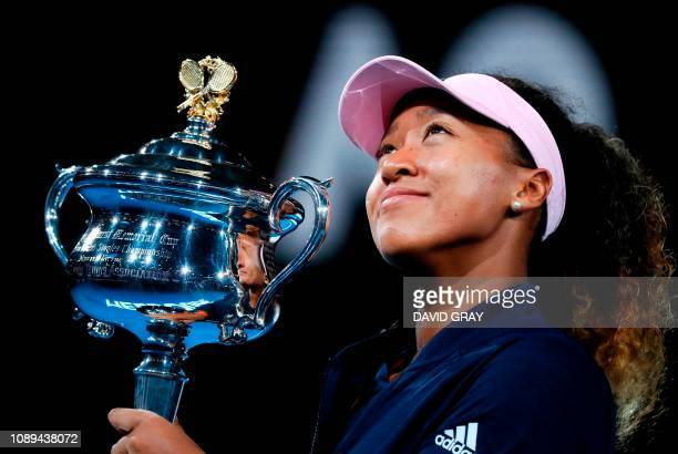 TOPSHOT Japan's Naomi Osaka celebrates with the championship trophy during the presentation ceremony after her victory against Czech Republic's Petra...