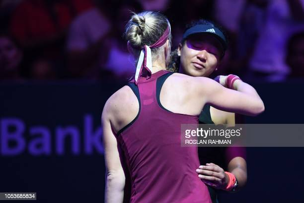 Japan's Naomi Osaka hugs Kiki Bertens of the Netherlands after retiring with an injury during their singles match at the WTA Finals tennis tournament...