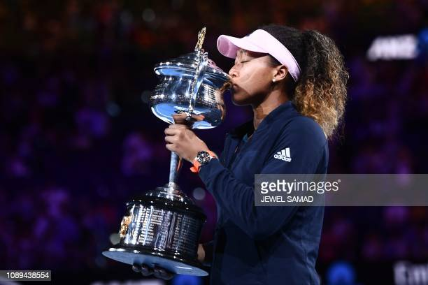 TOPSHOT Japan's Naomi Osaka poses with the championship trophy during the presentation ceremony after her victory against Czech Republic's Petra...