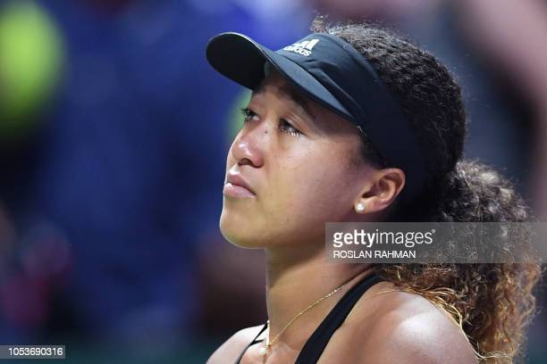 Japan's Naomi Osaka reacts after retiring during her singles match against Kiki Bertens of the Netherlands at the WTA Finals tennis tournament in...