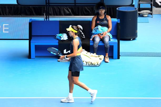 Japan's Naomi Osaka takes rest between the games as her opponent Spain's Garbine Muguruza walks back to her seat during their women's singles match...