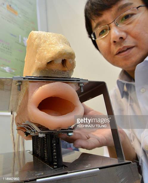 Japan's national Kagawa University professor Hideyuki Sawada displays his talking and singing robot which has motorcontrolled organs such as vocal...