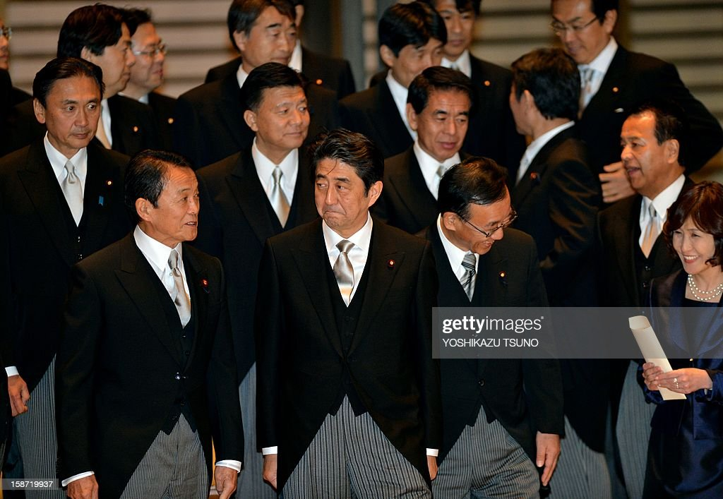 Japan's new Prime Minister Shinzo Abe (C), accompanied by Finance Minister Taro Aso (3L) and Justice Minister Sadakazu Tanigaki (2nd R), waits for his vehicle after a photo session with his cabinet members as they were inaugurated before Emperor Akihito at the Imperial Palace in Tokyo on December 26, 2012. Abe was elected Japan's prime minister by the lower house of parliament after he swept to power on a hawkish platform of getting tough on diplomatic issues while fixing the economy. AFP PHOTO / Yoshikazu TSUNO