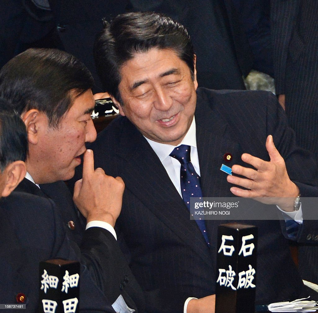Japan's new Prime Minister Shinzo Abe (R) chats to Shigeru Ishiba (L), secretary general of the ruling Liberal Democratic Party, during a plenary session of the lower house at parliament in Tokyo on December 27, 2012. Abe was elected Japan's prime minister by the lower house of parliament on December 26 after he swept to power on a hawkish platform of getting tough on diplomatic issues while fixing the economy.