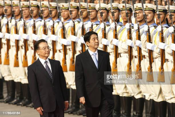 Japan's new Prime Minister Shinzo Abe together with Chinese Premier Wen Jiabao inspect the honour guard during a welcoming ceremony at the east gate...