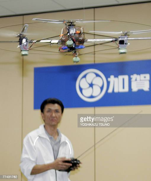 Japan's Nippon Engineering College robot engineer Gentaro Matuura demonstrates a radio controled flying robot which has four rotors two are counter...