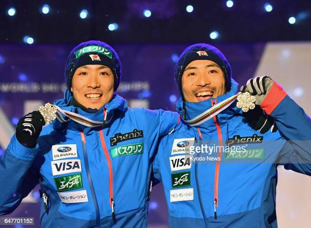 Japan's Nordic combined skiers Akito Watabe and his younger brother Yoshito celebrate after claiming the men's team sprint bronze at the Nordic world...