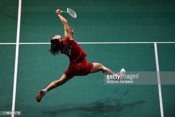 TOPSHOT Japan's Nozomi Okuhara hits a return against India's Saina Nehwal during their women's singles match at the Singapore Open badminton...