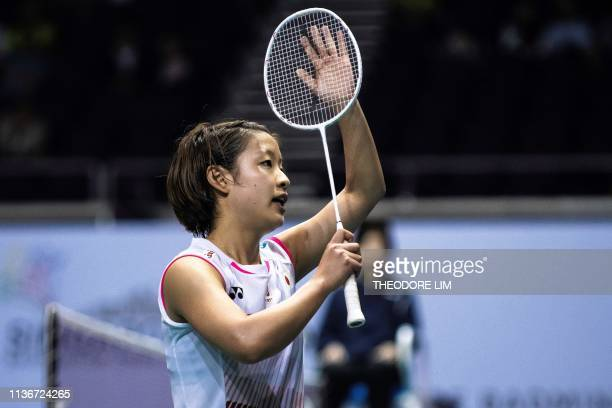 Japan's Nozomi Okuhara reacts after defeating India's Pusarla V Sindhu during their women's singles semifinal match at the Singapore Open badminton...