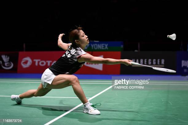 Japan's Nozomi Okuhara returns a shuttlecock to Thailand's Ratchanok Intanon during her women's singles semi final match at the BWF Badminton World...