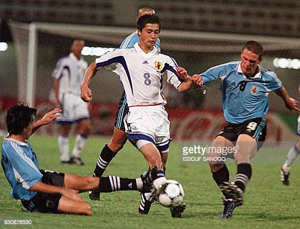 Japan's Ogasawara Misuo and Uruguay's Perez Diego go for the ball as Japan qualified 21 for the final of the FIFA Under20 world championship 21 April...