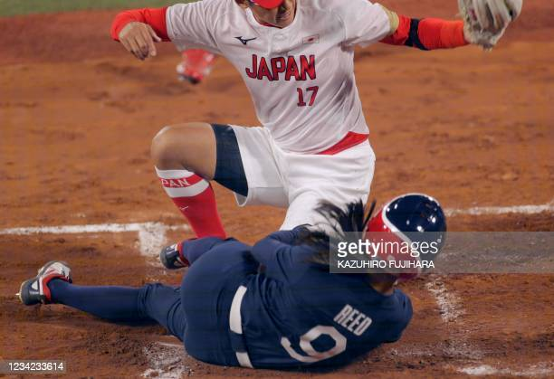 Japan's pitcher Yukiko Ueno tags out USA's Jannet Reed at home plate during the first inning of the Tokyo 2020 Olympic Games softball gold medal game...