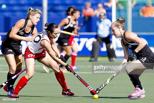 Japan's player Yoshino Kasahara vies for the ball with New Zealand's players Jordan Grant and Samantha Charlton during the Field Hockey World Cup...