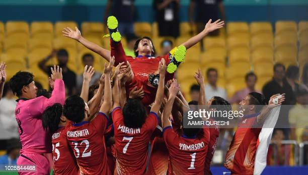 Japan's players celebrate after their victory against Malaysia during the medals ceremony for the men's field hockey final match between Japan and...