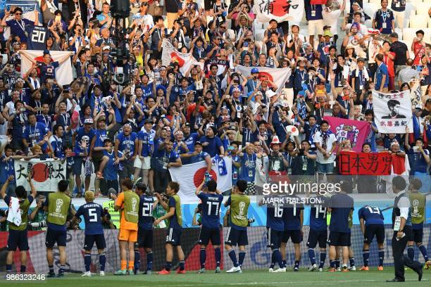 TOPSHOT Japan's players celebrate their qualification for the next round at the end of the Russia 2018 World Cup Group H football match between Japan...