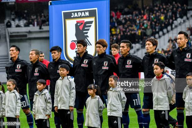 Japan's players line up with mascots for the national anthems ahead of a friendly football match between Japan and Brazil at The Pierre Mauroy...