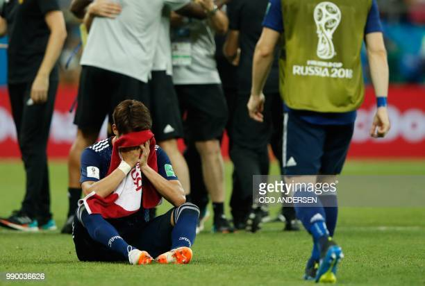 Japan's players look dejected at the end of the Russia 2018 World Cup round of 16 football match between Belgium and Japan at the Rostov Arena in...