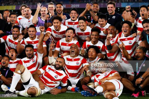 Japan's players pose for a group photo after winning the Japan 2019 Rugby World Cup Pool A match between Japan and Scotland at the International...