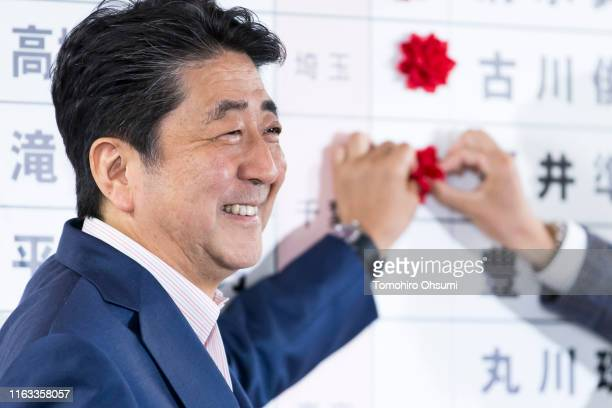 Japan's Prime Minister and ruling Liberal Democratic Party President Shinzo Abe places a red paper rose on a LDP candidate's name to indicate an...