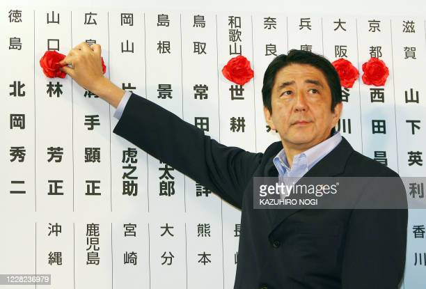 Japan's prime minister and ruling Liberal Democratic Party president, Shinzo Abe, puts a rosette on the name of an elected party member as votes are...