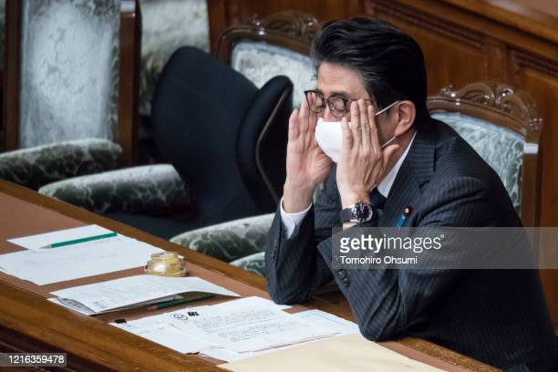 Japan's Prime Minister Shinzo Abe adjusts his face mask during an ordinary session at the upper house of parliament on April 02 in Tokyo, Japan. Abe...