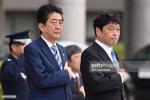 Japan's Prime Minister Shinzo Abe and Defence Minister Itsunori Onodera review the guard of honour at the Defence Ministry in Tokyo on September 11...