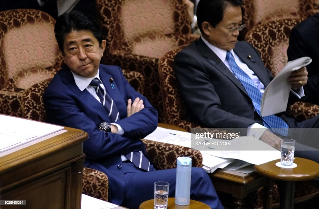 Japan's Prime Minister Shinzo Abe (L) and Finance Minister Taro Aso (R) attend an upper house budget committee session of parliament in Tokyo on March 8, 2018. Japan's prime minister warned March 8 that North Korea's offer of denuclearisation talks with the United States could be a ploy to play for time and stressed the need for Pyongyang to take 'concrete' steps. / AFP PHOTO / Kazuhiro NOGI