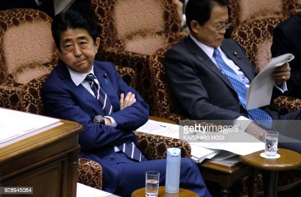 Japan's Prime Minister Shinzo Abe and Finance Minister Taro Aso attend an upper house budget committee session of parliament in Tokyo on March 8 2018...