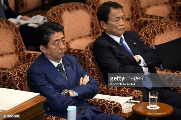 Japan's Prime Minister Shinzo Abe and Finance Minister Taro Aso attend a upper house budget committee session at parliament in Tokyo on March 14 2018...