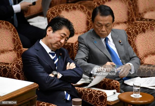 Japan's Prime Minister Shinzo Abe and Finance Minister Taro Aso attend a budget committee session of the upper house in Tokyo on March 19 2018...