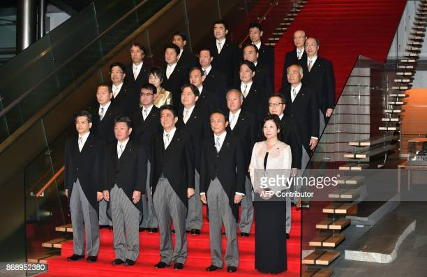 Japan's Prime Minister Shinzo Abe and his cabinet members pose during a photo session following their first cabinet meeting at Abe's official...