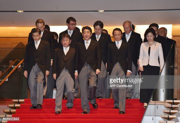 Japan's Prime Minister Shinzo Abe and his cabinet members walk down the stairs prior to a photo session following their first cabinet meeting at...
