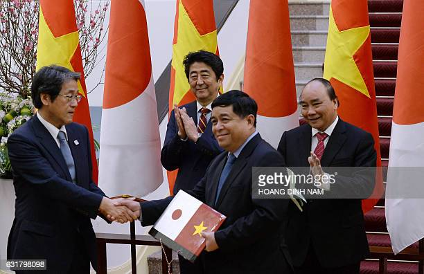 Japan's Prime Minister Shinzo Abe and his Vietnamese counterpart Nguyen Xuan Phuc clap as Vietnam's Minister of Planning and Investments Nguyen Chi...