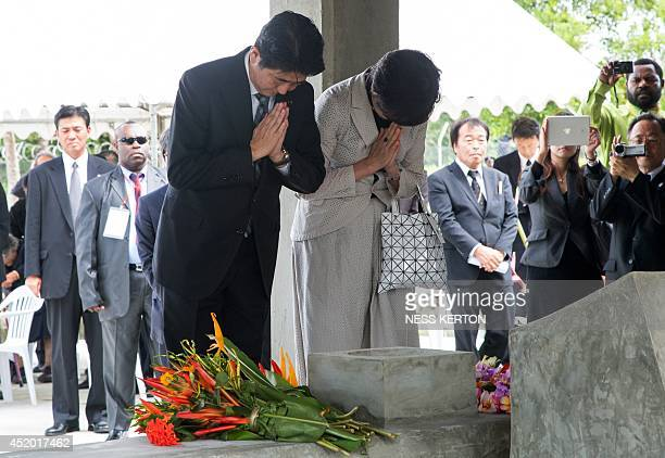 Japan's Prime Minister Shinzo Abe and his wife Akie pay their respects at a peace park in Wewak in Papua New Guinea on July 11 2014 Abe is visiting...