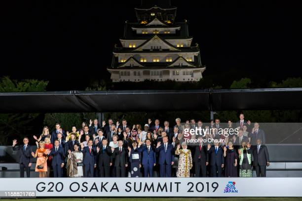 Japan's Prime Minister Shinzo Abe and other world leaders pose for a family photograph with their partners in front of Osaka Castle at the G20 summit...