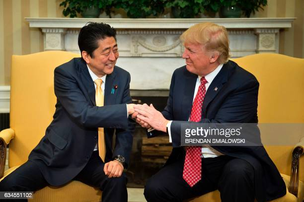 Japan's Prime Minister Shinzo Abe and US President Donald Trump shake hands before a meeting in the Oval Office of the White House on February 10...