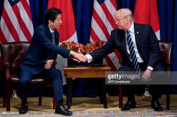Japan's Prime Minister Shinzo Abe and US President Donald Trump shake hands before a meeting at the Palace Hotel during the 72nd United Nations...