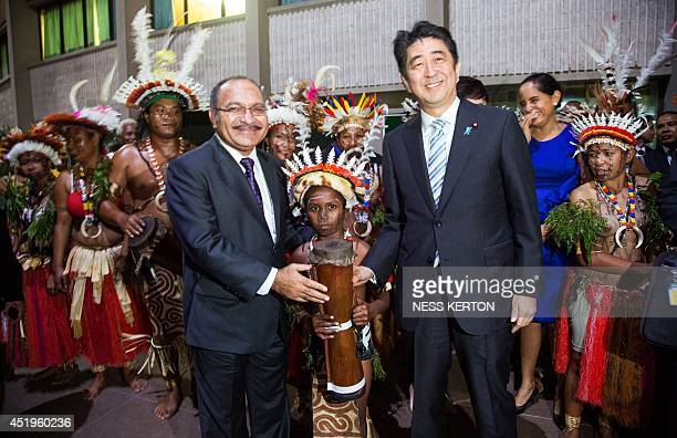Japan's Prime Minister Shinzo Abe and with Papua New Guinea Prime Minister Peter O'Neil join locals playing the drums before attending an offical...