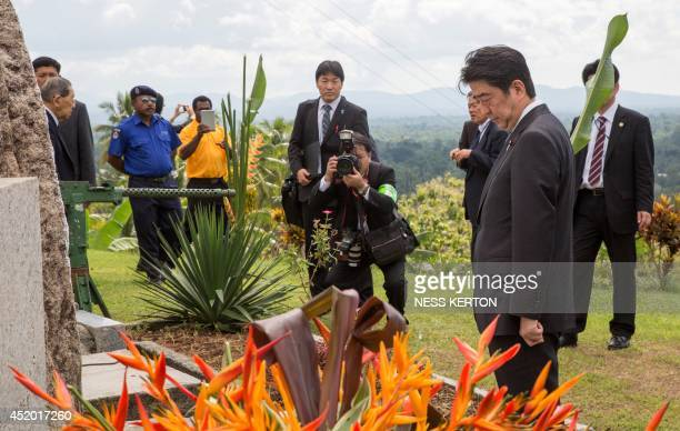 Japan's Prime Minister Shinzo Abe attends a war memorial at Wewak in Papua New Guinea on July 11 2014 Abe is visiting New Zealand Australia and Papua...